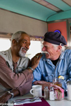 A black man and a white man, both seniors, happily engaged in conversation at a dinner in a diner.  Both men have gray hair, the black man has a beard and the white man has a mustache.  These two seniors have been the best of friends for many years.